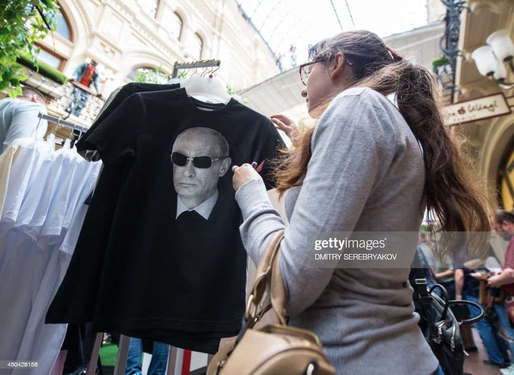 A wiman looks at one of the T-shirts with images of Russia's President Vladimir Putin being displayed for sale at GUM, one of the oldest department stores in central Moscow, on June 11, 2014.