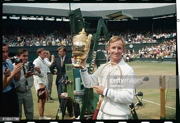 Rod Laver flashes a winning smile as he holds the loving cup high after defeating fellow Australian Tony Roche 63 64 62 for the men's singles title...