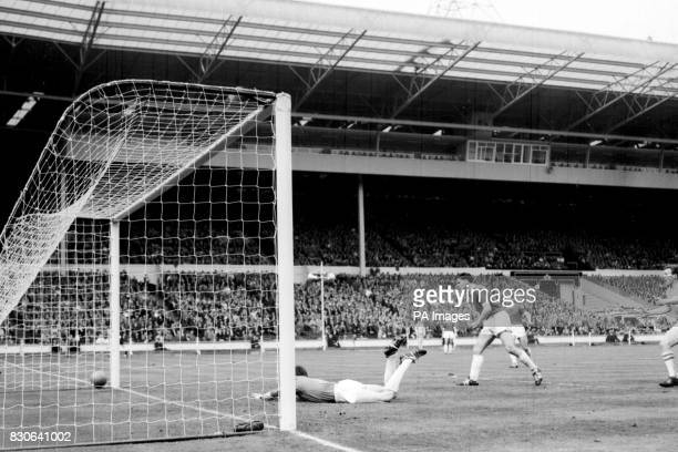 Wimbledon goalkeeper Mike Kelly dives in vain but cannot keep out Sutton United's Mike Goodall's shot during the FA Amateur Cup final at Wembley...