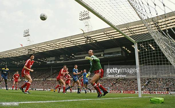Wimbledon player Lawrie Sanchez flicks a header past Liverpool goalkeeper Bruce Grobelaar despite the attentions of central defender Gary Ablett to...