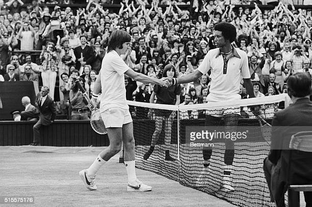 Artur Ashe USA and Jimmy Connors USA shake hands over the net here 7/5 after Ashe had won the men's singles title with score 61615764 7/5/1975