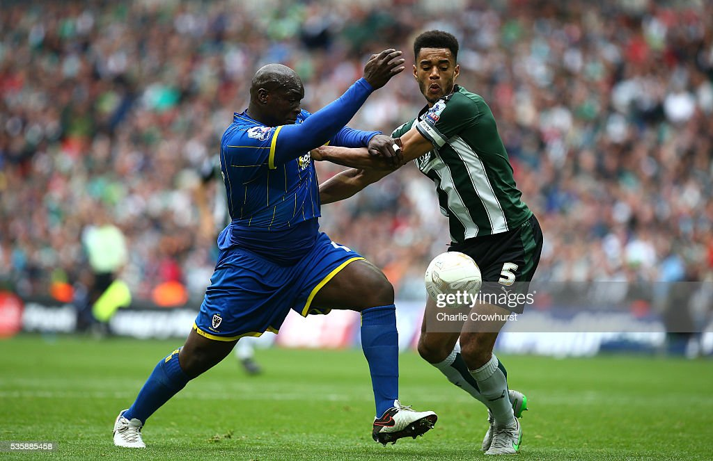 AFC Wimbledon's Adebayo Akinfenwa battles for the ball with Plymouth's Curtis Nelson during the Sky Bet League 2 Play Off Final between Plymouth Argyle and AFC Wimbledon at Wembley Stadium on May 30, 2016 in London, England.
