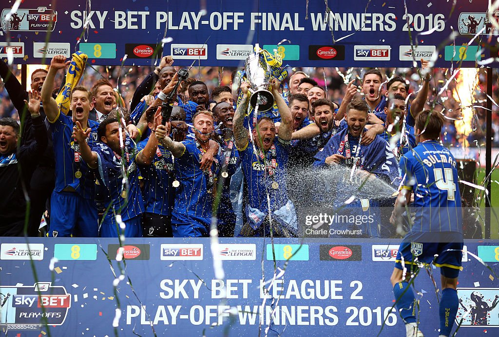 AFC Wimbledon's Barry Fuller lifts the trophy high as he celebrates the team win and promotion with team mates during the Sky Bet League 2 Play Off Final between Plymouth Argyle and AFC Wimbledon at Wembley Stadium on May 30, 2016 in London, England.