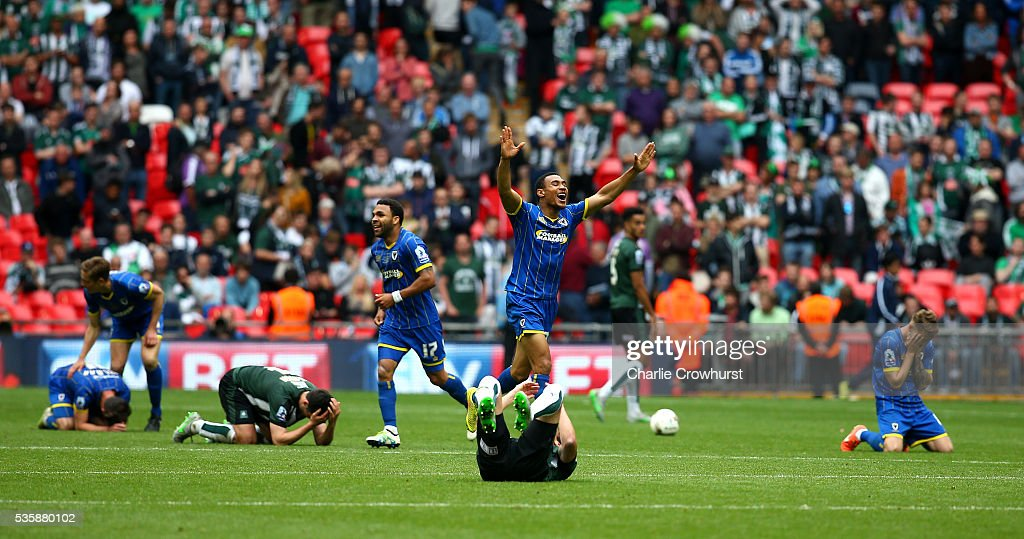 AFC Wimbledon's Darius Charles celebrates the teams win at the final whistle as Plymouth players collapse to the floor dejected during the Sky Bet League 2 Play Off Final between Plymouth Argyle and AFC Wimbledon at Wembley Stadium on May 30, 2016 in London, England.