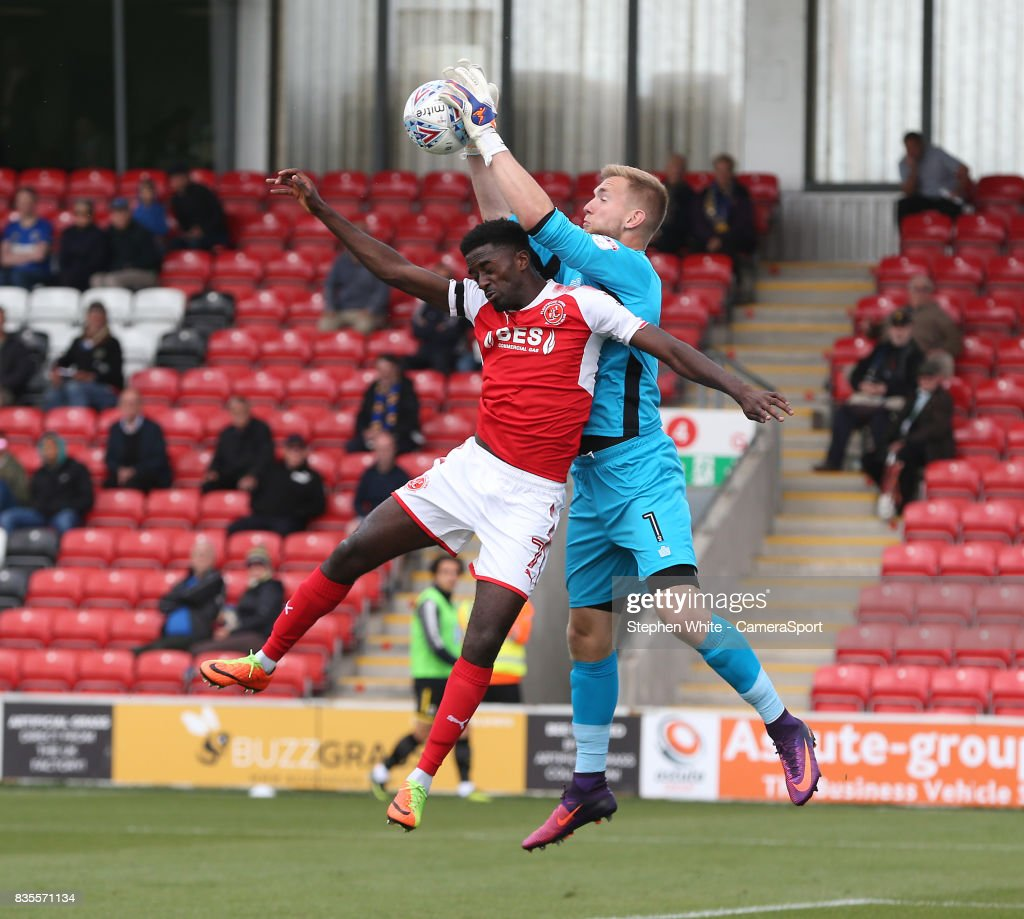 Wimbledon's goalkeeper George Long collects the ball despite the attentions of Fleetwood Town's Jordy Hiwula during the Sky Bet League One match between Fleetwood Town and A.F.C. Wimbledon at Highbury Stadium on August 19, 2017 in Fleetwood, England.