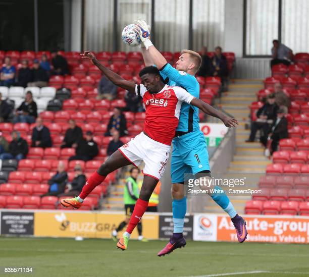 Wimbledon's goalkeeper George Long collects the ball despite the attentions of Fleetwood Town's Jordy Hiwula during the Sky Bet League One match...