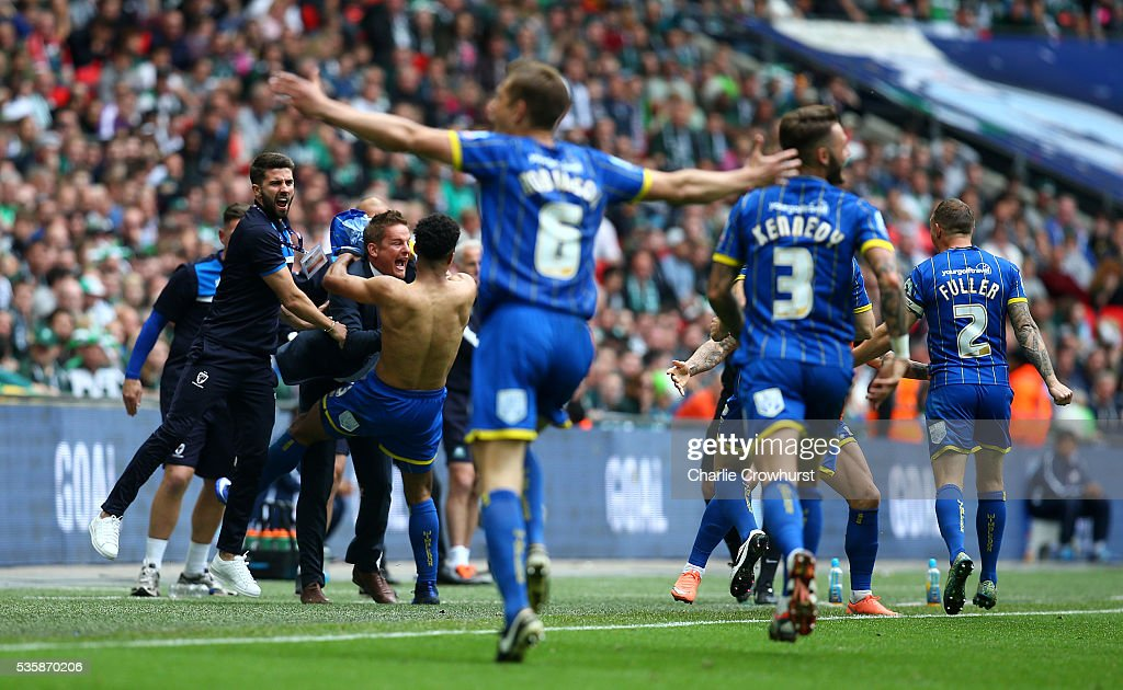 AFC Wimbledon's Lyle Taylor celebrates scoring the first goal of the game with manager Neal Ardley during the Sky Bet League 2 Play Off Final between Plymouth Argyle and AFC Wimbledon at Wembley Stadium on May 30, 2016 in London, England.