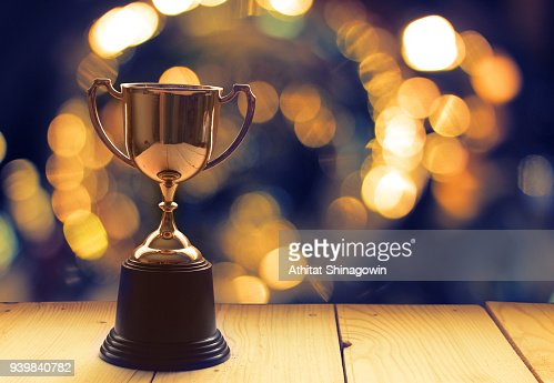 Win prize trophy on wood table with background window. : Stock Photo