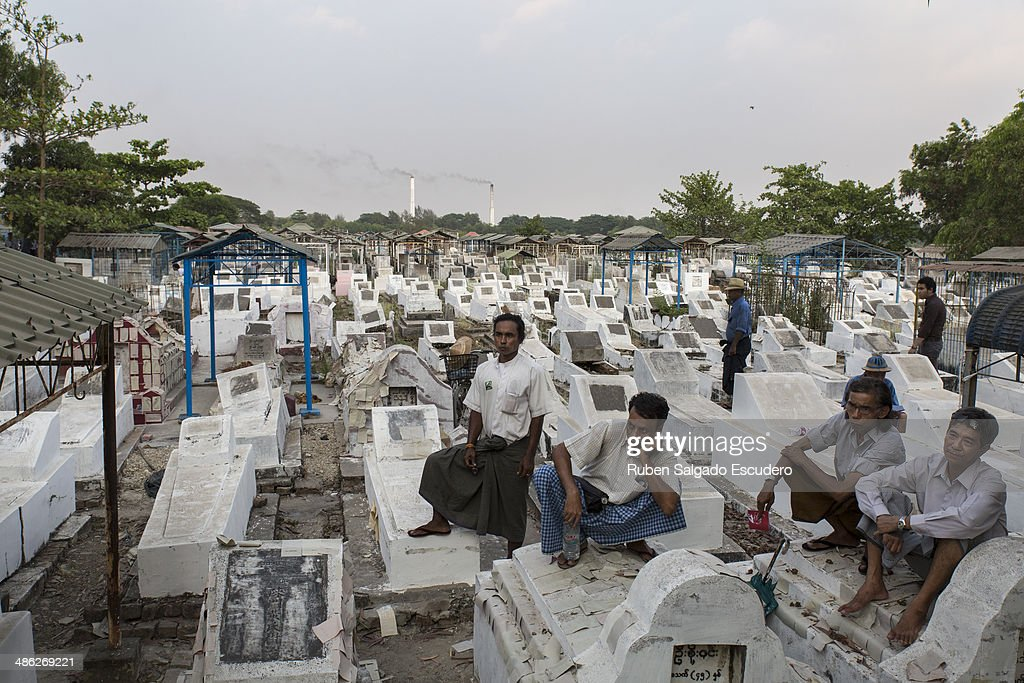 Win Tin followers take a rest on tombstones during Win Tin's memorial service in Yay Way cemetery on April 23, 2014 in Yangon, Burma.The Burmese journalist who helped Aung San Suu Kyi launch a pro-democracy movement against the junta military regime, died April 21 in Rangoon.