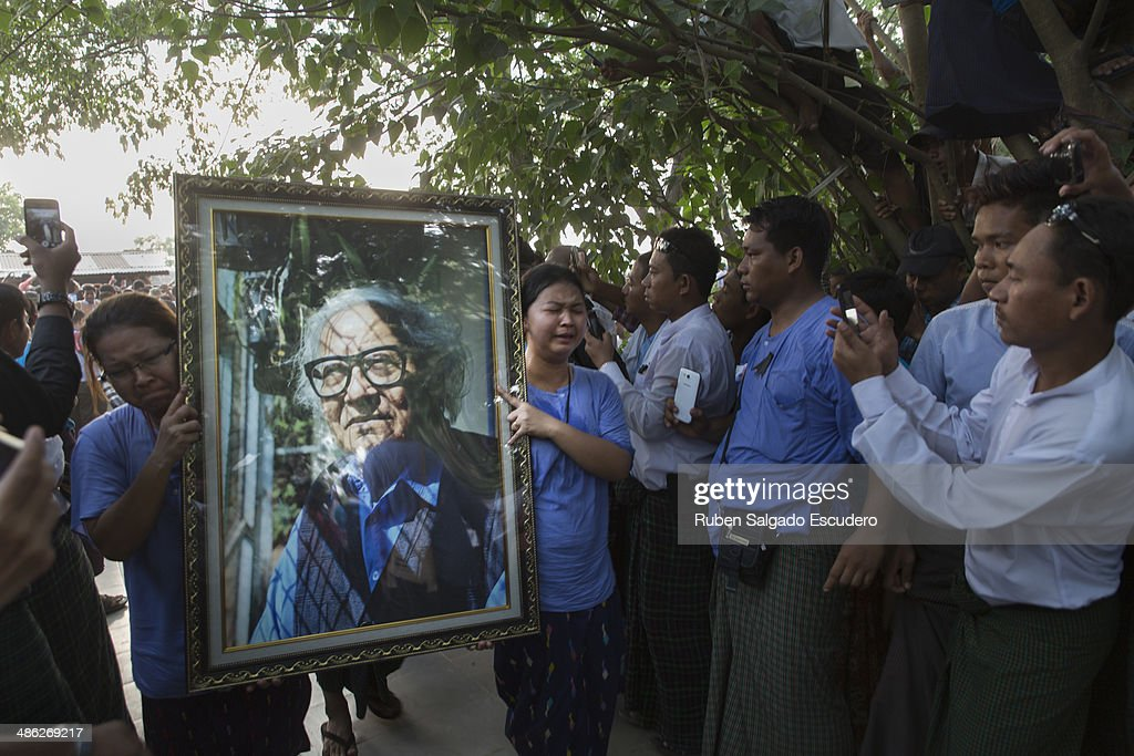 Win Tin's family members carry a large photo towards his tombstone during his funeral in Yay Way cemetery on April 23, 2014 in Yangon, Burma. The Burmese journalist who helped Aung San Suu Kyi launch a pro-democracy movement against the junta military regime, died April 21 in Rangoon.