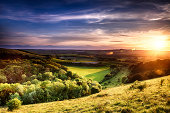 Winchester hill sunset across folding farmland and trees