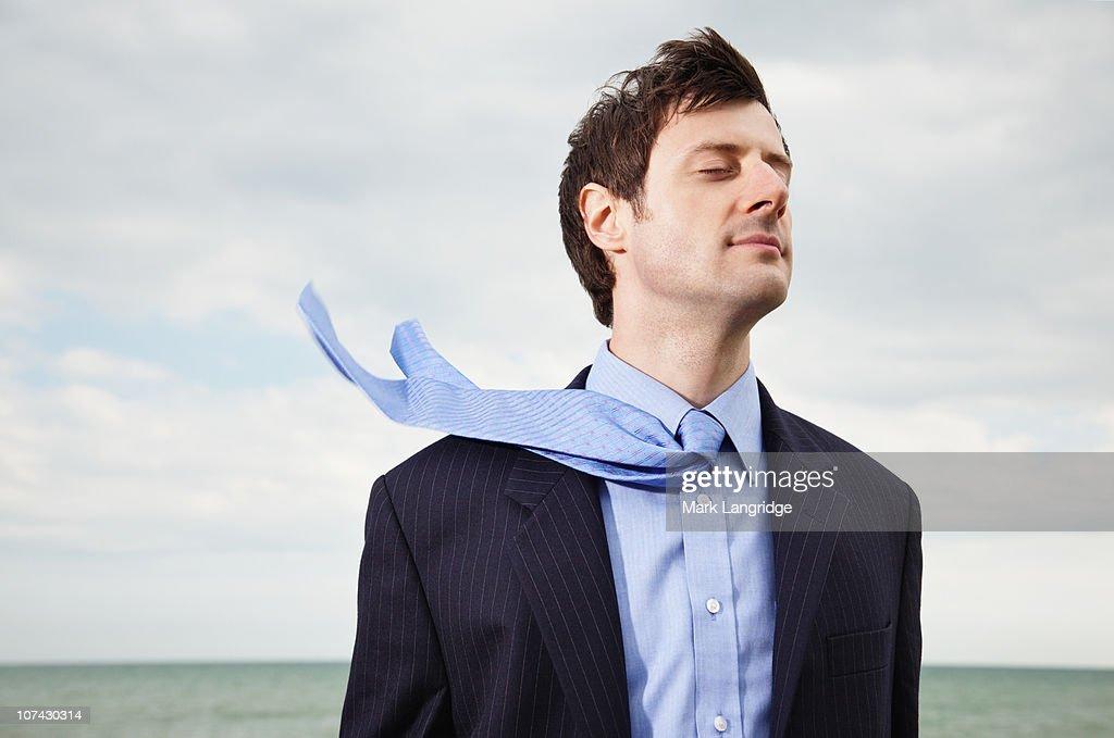 Wind blowing businessmans necktie near ocean : Stock Photo