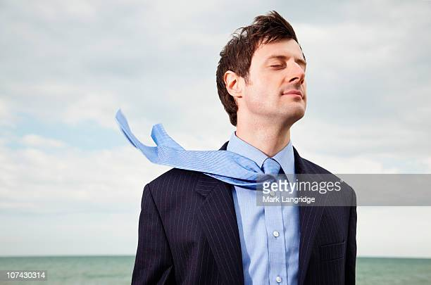 Wind blowing businessmans necktie near ocean