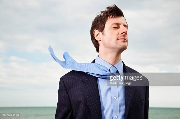 Wind blowing businessmans necktie near ocean