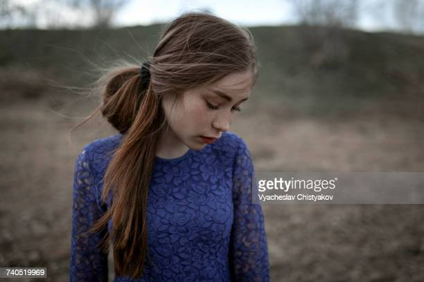 Wind blowing hair of pensive Caucasian woman