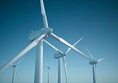 White wind turbine generating electricity on blue sky