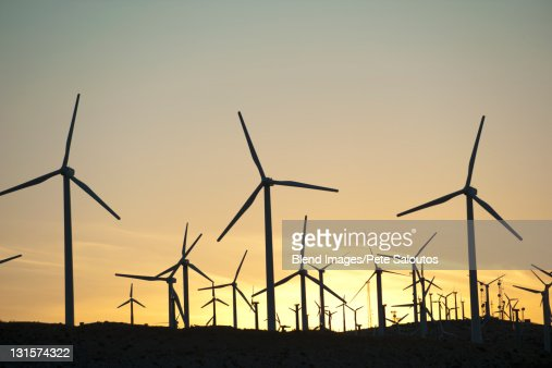Wind farm in desert at sunset : Stock Photo