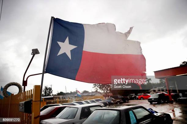 Wind from Hurricane Harvey batters a Texas flag on August 26 2017 in Houston Texas Harvey which made landfall north of Corpus Christi late last night...