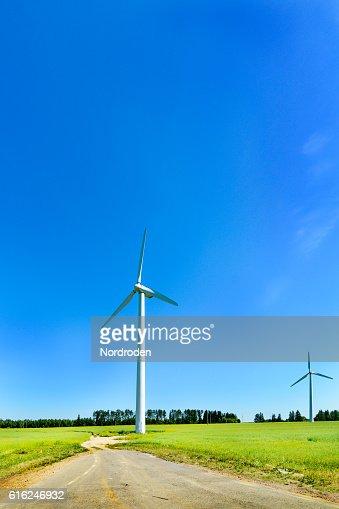 Wind generator in the meadows, on a background of blue : Foto de stock