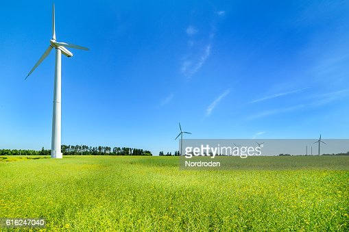 Wind generator in the meadows, on a background of blue : Foto de stock