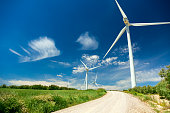 Wind Generator Turbines in beautiful Real Landscape with grass and road - renewable energy concept , horizontal