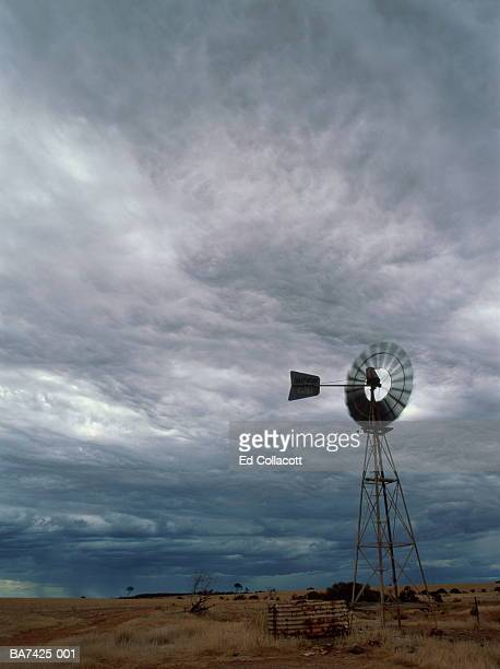 Wind powered water pump, storm clouds overhead, Australia