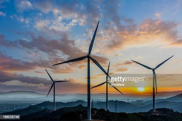 Turbina de vento na sunset e torres de energia