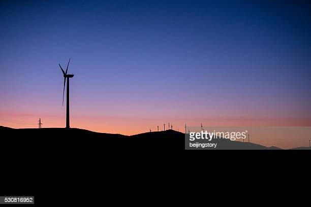 wind turbines against red and orange sunset