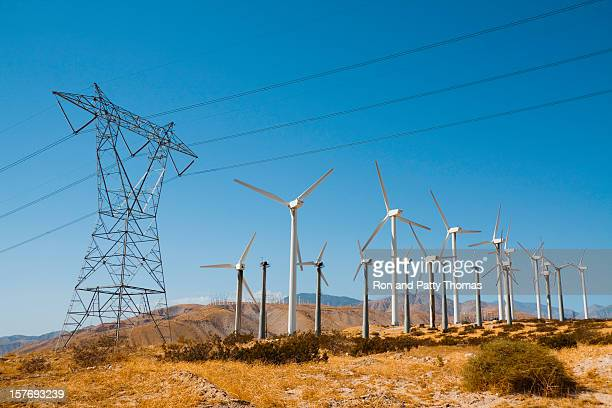 Wind turbines and pylon against a blue sky