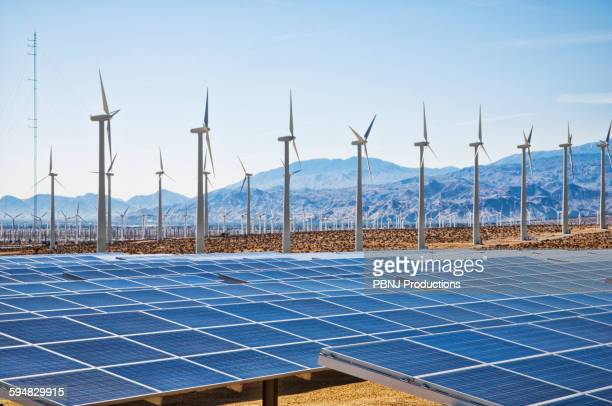 Wind turbines and solar panels in remote landscape