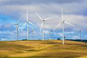 Group of windmills in a wind farm creating renewable energy with cows grazing beneath in Taralga NSW Australia.