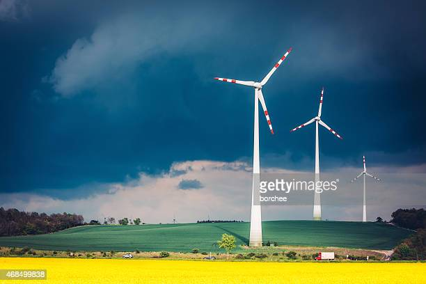 Wind Turbines In Colorful Fields On A Windy Day