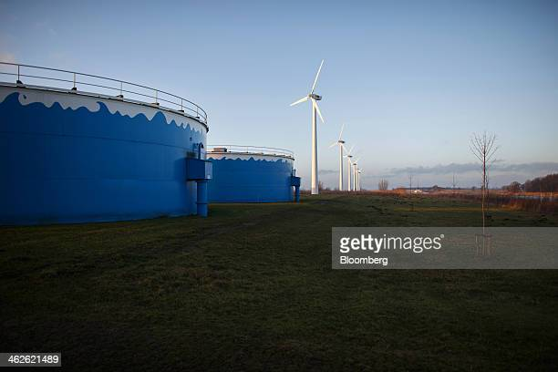 Wind turbines manufactured by Nuon Energy NV a unit of Vattenfall AB stand beside clean drinking water storage silos at Vitens NV's ground water...
