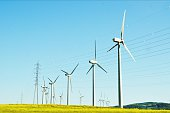 Wind Turbines On Grassy Field Against Clear Blue Sky