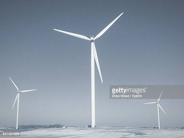 Wind Turbines On Snow Covered Landscape Against Clear Sky
