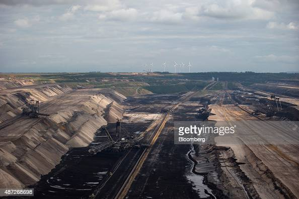 Wind turbines operate beyond an open pit lignite mine also known as brown coal operated by RWE AG in Hambach Germany on Monday 7 Sept 2015 German...