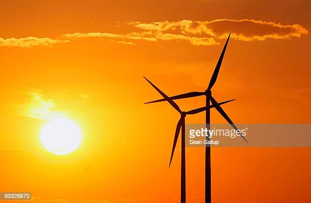 Wind turbines spin as the sun sets August 4 2005 near Schoenwalde in eastern Germany The ruling Social Democrats the SPD who are in a coalition with...