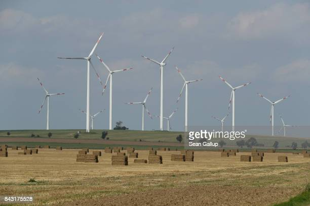 Wind turbines spin at a windpark near a field covered in bales of hay on August 25 2017 near Groeningen Germany Germany is making strong progress in...