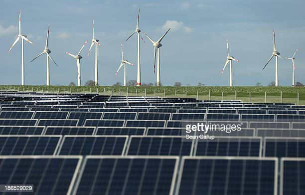 Wind turbines stand behind a solar power park on October 30 2013 near Werder Germany The German Social Democrats and Christian Democrats are...