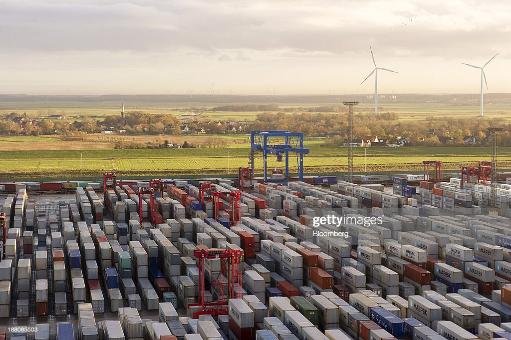Wind turbines stand beyond shipping containers standing at the Port of Bremerhaven seen from the Maersk Mc-Kinney Moeller Triple-E Class container ship, operated by A.P. Moeller-Maersk A/S, in Bremerhaven, Germany, on Monday, Nov. 11, 2013. A.P. Moeller-Maersk A/S's container-shipping line, the world's largest, reported an 11 percent increase in third-quarter profit after cost cuts countered a decline in freight rates. Photographer: Kristian Helgesen/Bloomberg via Getty Images