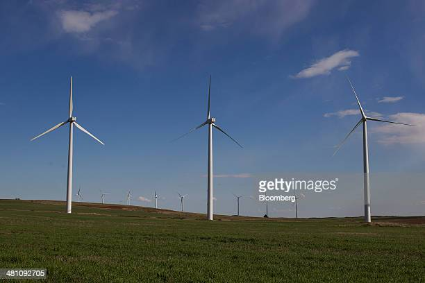 Wind turbines stand in green fields at the Vedadillo wind energy farm operated by Acciona SA in Navarra Spain on Thursday March 27 2014 The Spanish...