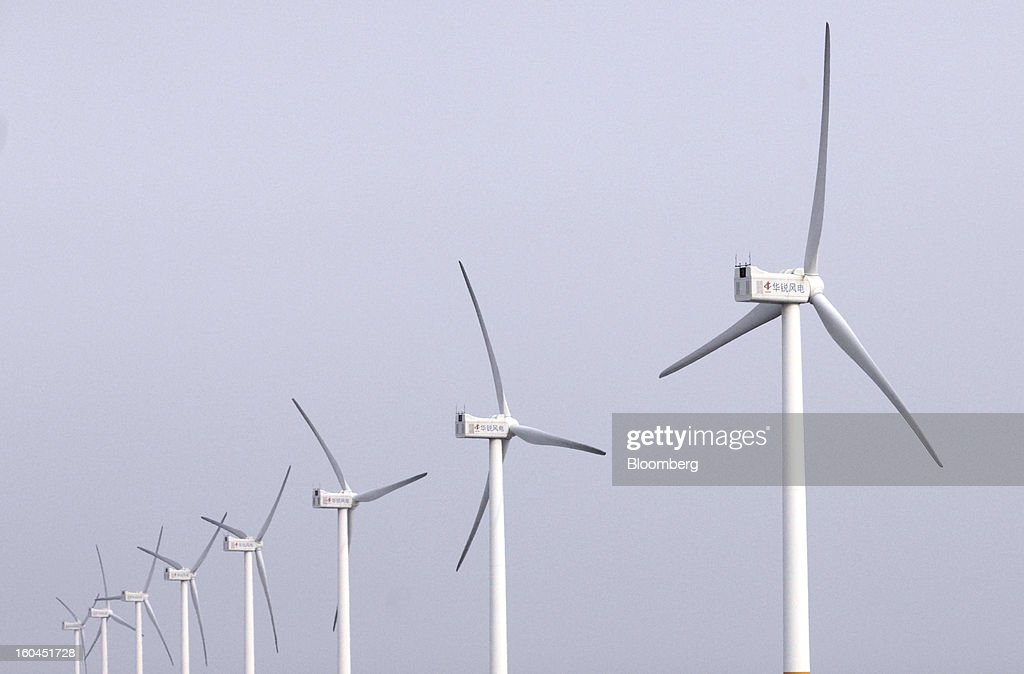 Wind turbines stand on the sea near the Yangshan Deep Water Port in Shanghai, China, on Thursday, Jan. 31, 2013. China's economic growth accelerated for the first time in two years as government efforts to revive demand drove a rebound in industrial output, retail sales and the housing market. Photographer: Tomohiro Ohsumi/Bloomberg via Getty Images