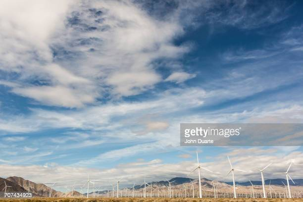 Wind turbines under cloudy sky in remote landscape