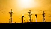 Wind turbines with pylon at sunset
