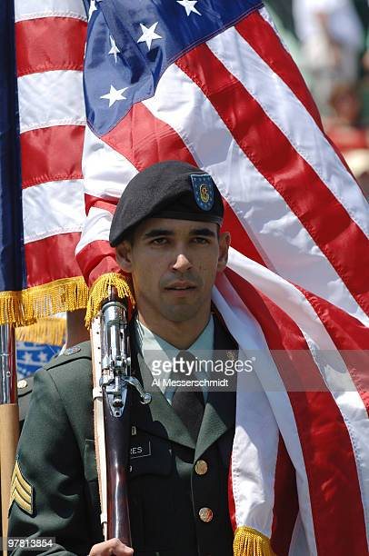 A windblown American flag drapes a soldier during the National Anthem at the 2006 NASDAQ100 women's tennis final April 1 Key Biscayne Florida...