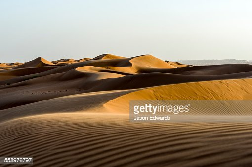 Windblown ripples and sand patterns on the surface of a red sand dune at sunset.