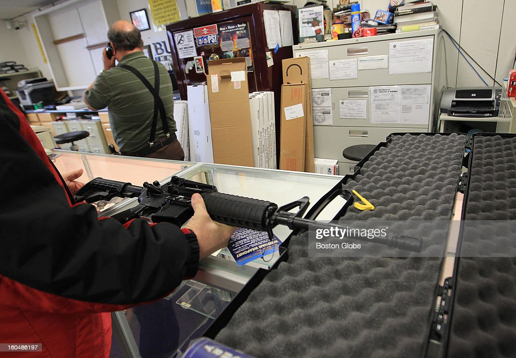 A Windham Weaponry sporting rifle is sold soon after arriving in store. Ted Oven, left, owner of Northeast Trading Co., Inc., has had a hard time keeping guns in stock because of the skyrocketing demand.