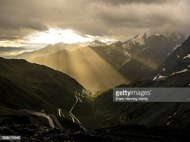 Winding mountain road with dramatic sky