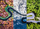 Winding road in the forest. Autumn, summer and winter time colage. Top down aerial view from a drone.