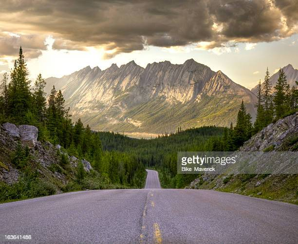 Winding road towards distant mountains at beautiful sunrise